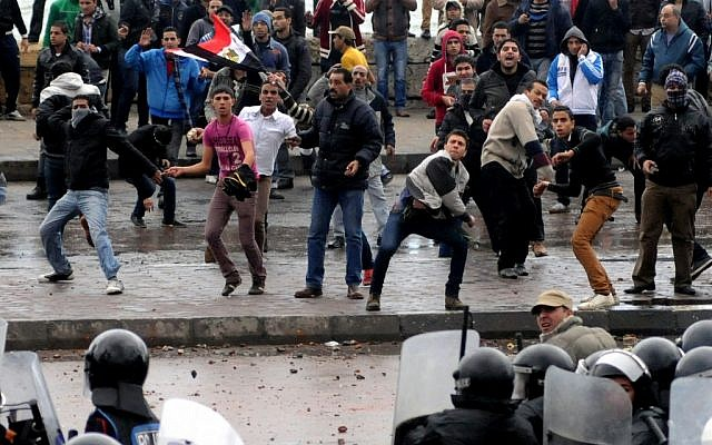 Opponents of Egyptian President Mohammed Morsi clash with Islamist supporters of the president, unseen, as a cordon of riot police separates the groups in Alexandria, Egypt, Friday, Dec. 21 (photo credit: AP)