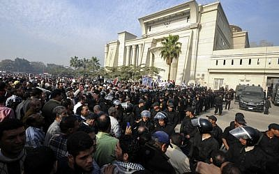 Riot police form a cordon as several thousand supporters of Islamist President Mohammed Morsi surround the Supreme Constitutional Court on Sunday (photo credit: Ahmad Hammad/AP).