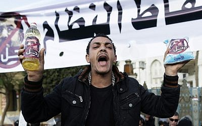 An Egyptian protester  chants anti-Muslim Brotherhood and Egyptian President Mohammed Morsi slogans outside the presidential palace under a banner with a defaced picture of president Mohammed Morsi and Arabic that reads 'the people want to bring down the regime,' in Cairo, Egypt, Saturday. (AP Photo/Hassan Ammar)