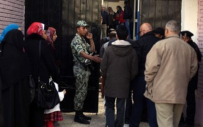 An Egyptian soldier stands guard outside a polling station in Cairo, Egypt, on Saturday as people line up to cast their votes in a referendum on a disputed constitution drafted by Islamist supporters of President Mohammed Morsi (photo credit: AP/Khalil Hamra)