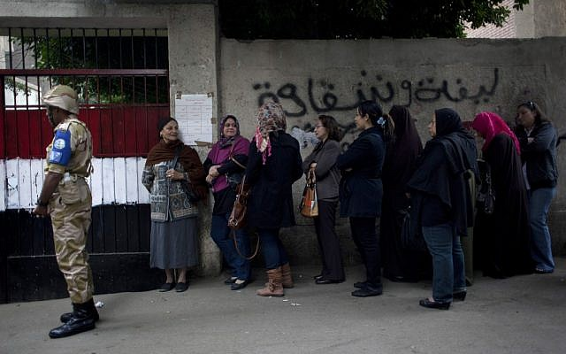 An Egyptian soldier stands guard outside a polling center as women stand in line to cast their votes during a referendum on a disputed constitution drafted by Islamist supporters of President Mohammed Morsi, in Cairo, Egypt, on Saturday, December. 15, 2012. (photo credit: AP Photo/Nasser Nasser)