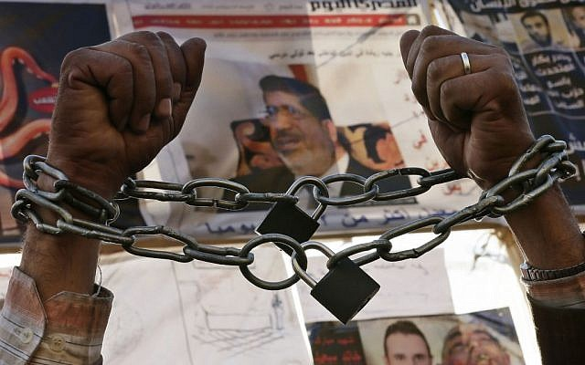 A protester chains his hands during a protest in Tahrir Square in Cairo, Egypt, Monday, Dec. 17, 2012. (photo credit: Hassan Ammar/AP)