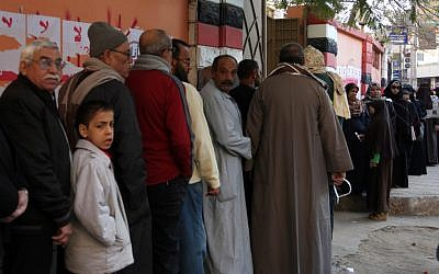 Egyptians line up outside a polling station as they wait their turn to cast their votes in the second round of a referendum on a disputed constitution drafted by Islamist supporters of President Mohammed Morsi in Fayoum, about 100 kilometers (62 miles) south of Cairo on Saturday, December 22. (photo credit: AP/Khalil Hamra)