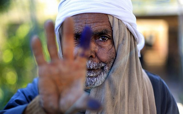 An Egyptian elderly man shows his inked finger after casting his vote in the second round of a referendum on a disputed constitution drafted by Islamist supporters of President Mohammed Morsi in Fayoum, Egypt, on Saturday. (photo credit: AP/Khalil Hamra)
