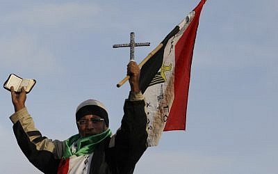 An Egyptian protester holds the Quran, a Cross, and the Egyptian national flag during a demonstration in front of the presidential palace in Cairo on Tuesday, December 11, 2012 (photo credit: Petr David Josek/AP)