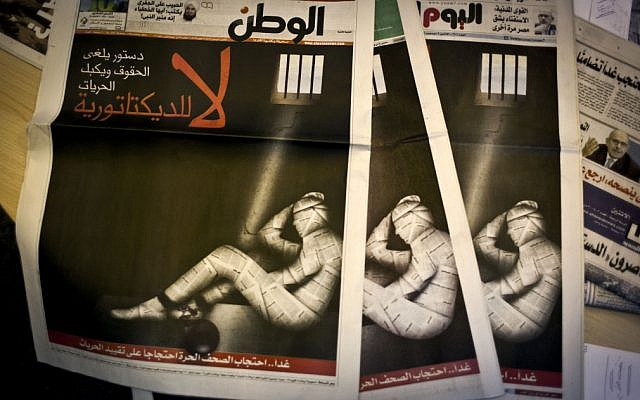 Copies of Egypt's most prominent newspapers running black background front pages with Arabic text that reads, 'No to dictatorship. Tomorrow, free newspapers will... protest freedom's restrictions' and a picture of a man wrapped in newspaper with his feet cuffed, at the editorial room of Al Masry Al Youm daily newspaper in Cairo on Monday, December 3, 2012. (photo credit: Nasser Nasser/AP)