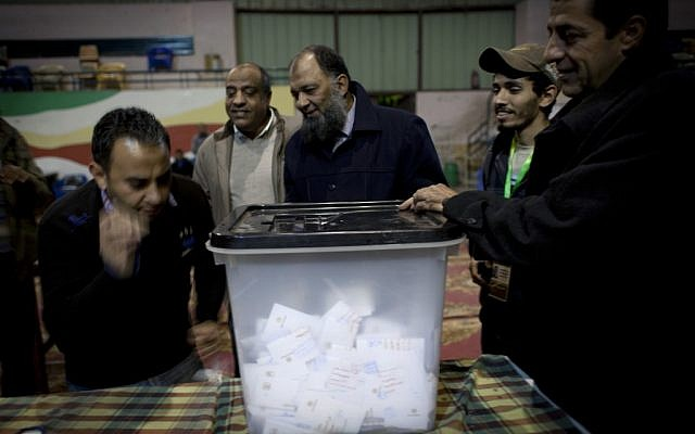 Egyptian election workers at a polling station in Giza, Egypt unseal a ballot box for counting at the end of the second round of the referendum for the Islamist-backed constitution on December 22, 2012. (photo credit: Nasser Nasser/AP)