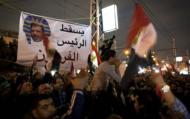 Egyptian protesters carry national flags and chant anti-Muslim Brotherhood slogans during a demonstration in front of the presidential palace in Cairo, Egypt, on Tuesday, December 4, 2012 (photo credit: AP Photo/Nasser Nasser)