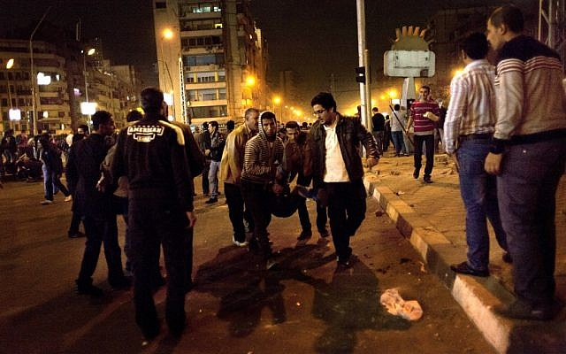 Demonstrators evacuate a wounded protester during anti-Morsi clashes in Cairo Wednesday night. (photo credit:AP/Nasser Nasser)