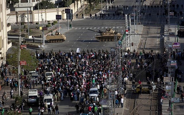 Egyptian army tanks secure the perimeter of the presidential palace while protesters gather chanting anti president Mohammed Morsi slogans, in Cairo, Egypt, on Friday, December 7. (photo credit: AP/Nasser Nasser)