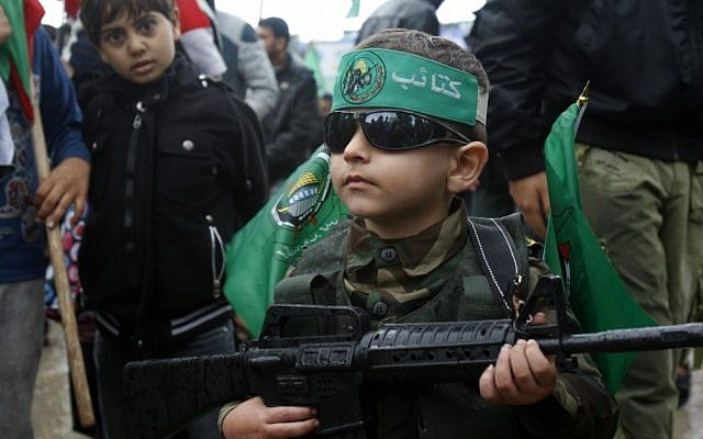 "A Palestinian boy wears a green headband with the Arabic slogan ""'Ezz Al-Din Al Qassam brigade"" and green Islamic flags while holding a toy gun during a rally to commemorate the 25th anniversary of the Hamas militant group, in Gaza City, December 2012. (photo credit: Adel Hana/AP)"