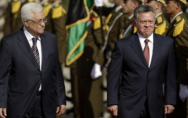 King Abdullah II of Jordan, right, and Palestinian Authority President Mahmoud Abbas, walk past honor guards prior to their meeting in the West Bank city of Ramallah, Thursday, Dec. 6 (photo credit: AP/Majdi Mohammed)