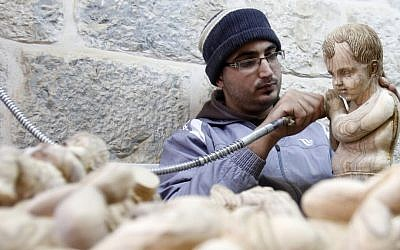 A Palestinian wood carver works on a figurine of the baby Jesus in an olive wood factory in the West Bank town of Bethlehem, ahead of Christmas, Friday, Dec. 21, 2012. (AP Photo/Nasser Shiyoukhi)