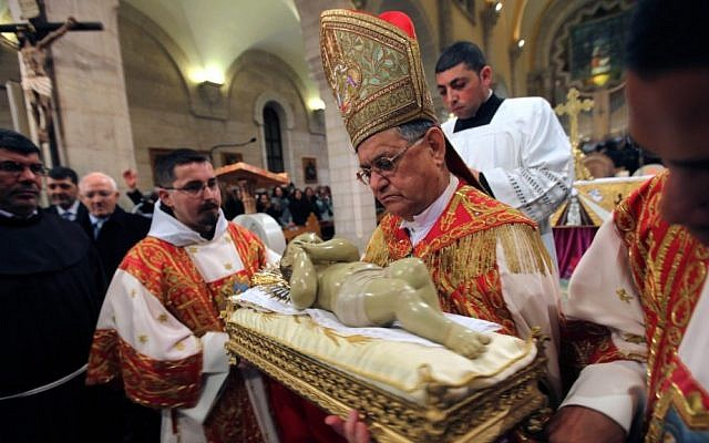 Latin Patriarch of Jerusalem Fouad Twal, center, holds a Baby Jesus statue in Saint Catherine's Church at the end of the Christmas Midnight Mass, and leads the procession to the Grotto, traditionally believed by Christians to be the birthplace of Jesus Christ, at the nearby Church of the Nativity, in Bethlehem on Tuesday, December 25, 2012. (photo credit: AP/Abed Al Hashlamoun, Pool)