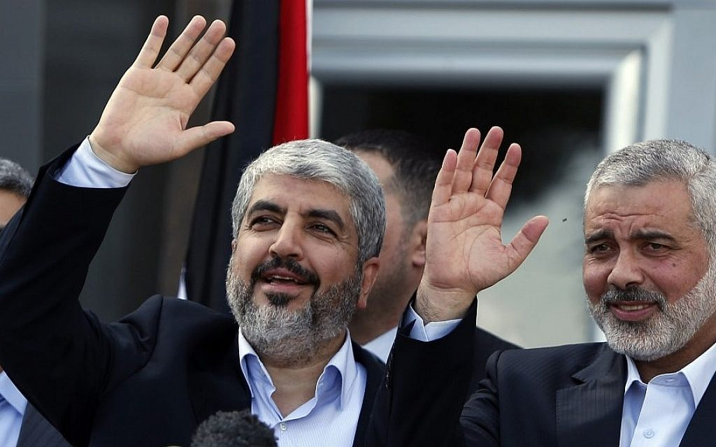 Hamas political bureau chief Khaled Mashaal, left, and Gaza's former Hamas Prime Minister Ismail Haniyeh wave during a news conference in the Gaza Strip in 2012. (AP/Suhaib Salem, Pool)