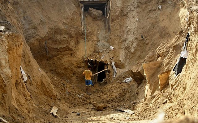 A Palestinian man works at the entrance of a destroyed smuggling tunnel along the Egypt Gaza border in Rafah, southern Gaza Strip, on November 27, 2012. (photo credit: AP Photo/Adel Hana, File)