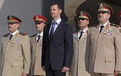 Syrian President Bashar Assad, center, stands next to Syrian Defense Minister Gen. Dawoud Rajha, right, and Chief of Staff Gen. Fahed al-Jasem el-Freij, left, during a ceremony to mark the 38th anniversary of the October 1973 Arab-Israeli war, in Damascus, Syria, in 2011. (AP Photo/SANA)
