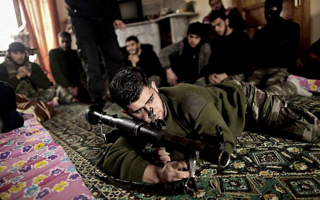 In this Monday, December 17, 2012 photo, Syrian rebels listen to their trainer teaching them how to use the RPG in Maaret Ikhwan, near Idlib, Syria (photo credit: AP/Mohammed Muheisen)