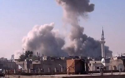 smoke rises from a building in Homs, Syria, after heavy shelling (photo credit: Shaam News Network via AP video)