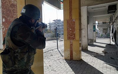 A Syrian soldier aims his rifle at free Syrian Army fighters during clashes in the Damascus suburb of Daraya, Syria, on Sunday, December 2, 2012 (photo credit: AP/SANA)