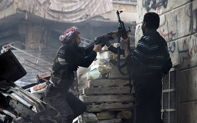 Free Syrian Army fighters fire at enemy positions during heavy clashes with government forces, in the Salaheddine district in Aleppo, Syria, on Saturday, Dec. 29 (photo credit: AP/Abdullah Al-Yasin)