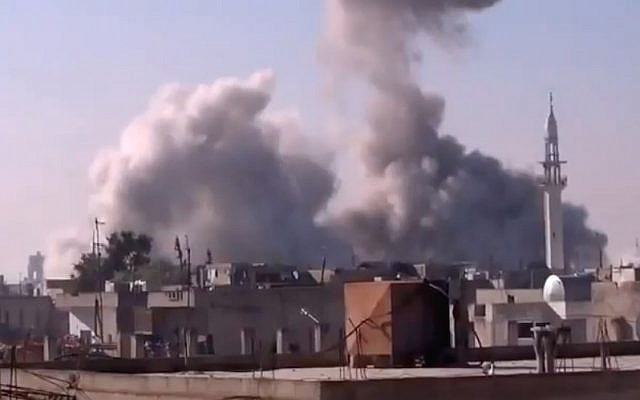 In this image, taken from video obtained from the Shaam News Network, which has been authenticated based on its contents and other AP reporting, smoke rises from buildings from heavy shelling in Homs, Syria on Thursday (photo credit: AP Photo/Shaam News Network via AP video)