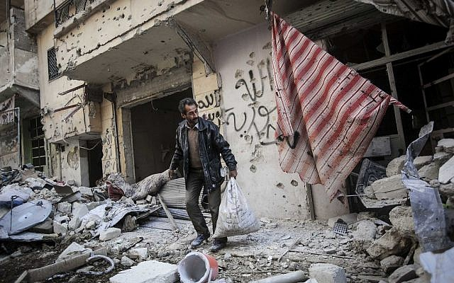 A man collects his belongings after his home was damaged due to heavy fighting between Free Syrian Army fighters and government forces in Aleppo, Syria, on Sunday, Dec. 2, 2012. (Narciso Contreras/AP)