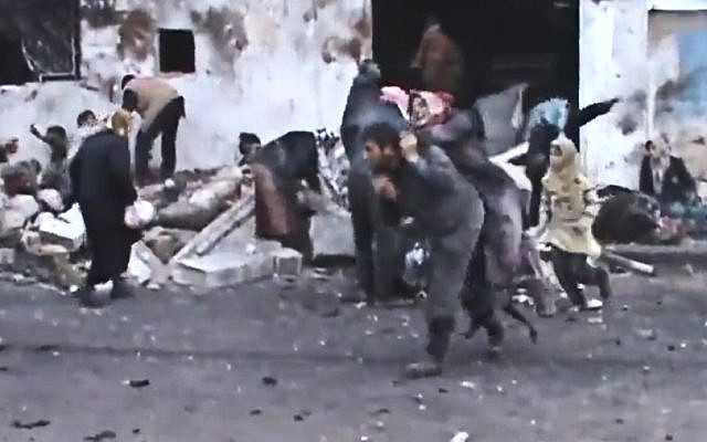 A Syrian man carries an elderly woman after a government airstrike hit the Hama suburb of Halfaya, Syria, on Sunday December 23, 2012. (photo credit: Shaam News Network via AP video)