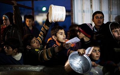 Syrian children wait in line for food at a refugee camp near the Turkish border, in Azaz, Syria, last December (photo credit: AP/Manu Brabo)