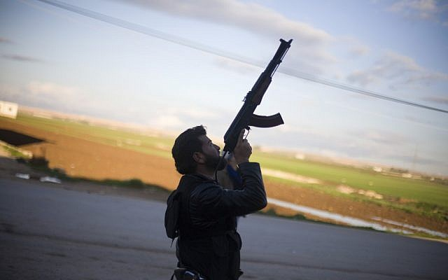 A Free Syrian Army fighter points his weapon as he watches a Syrian Army jet, not pictured, in Fafeen village, north of Aleppo province, Syria, on Tuesday, December 11, 2012. (photo credit: AP Photo/Manu Brabo)