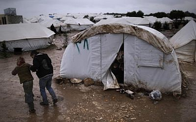 Children, who fled their home with their family, peek from their tent at a man helping a girl, after she fell on slippery ground, at a camp for displaced Syrians, in the village of Atmeh, Syria, Tuesday, Dec. 18, 2012. (photo credit: Muhammed Muheisen/AP)