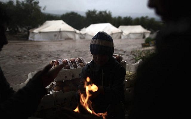 Syrians, who fled their homes with their families, gather around a fire to warm themselves at a makeshift vegetables store in a camp for the displaced in the village of Atmeh, Syria, Tuesday, Dec. 18, 2012. (Photo credit: AP/Muhammed Muheisen)