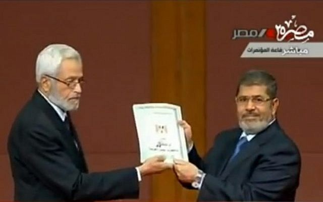 Egyptian President Mohammed Morsi receiving the new draft Egyptian constitution on Saturday. (photo credit: image capture from Egyptian national TV)