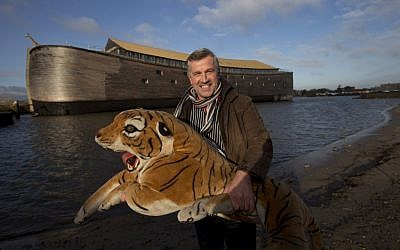 Johan Huibers poses with a stuffed tiger in front of the full scale replica of Noah's Ark in Dordrecht, Netherlands, Monday, Dec. 10, 2012. (Peter Dejong/AP)