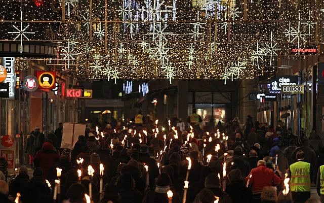 People walk with torches to protest against the awarding of the Nobel Peace Prize to the EU bloc in Oslo, Norway, Sunday December 9, 2012 (photo credit: AP/Yves Logghe)