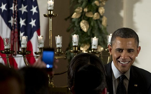 US President Barack Obama greets people as he stands next to a lit menorah during the Hanukkah reception in the Grand Foyer of the White House, Thursday, Dec. 13, 2012, in Washington. (Carolyn Kaster/AP)
