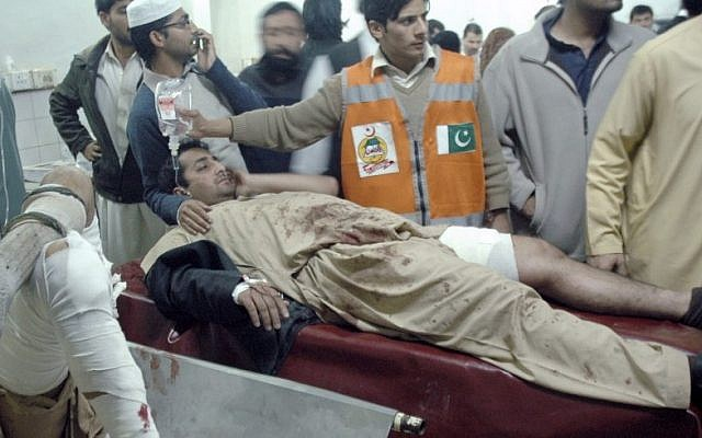 Injured victims of a suicide bombing are treated at a local hospital in Peshawar, Pakistan, Saturday, Dec. 22, 2012. A suicide bomber in Pakistan killed several people, including a provincial government official, at a political rally held Saturday by a party that has opposed the Taliban, officials said. (AP Photo/Mohammad Sajjad)