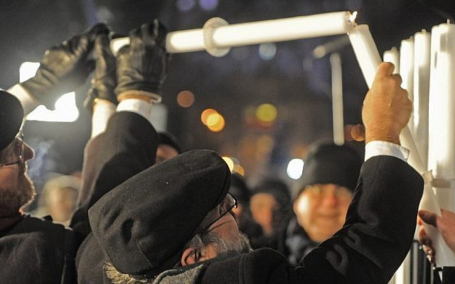 Poland's chief rabbi, Michael Schudrich, center, lights the first candle celebrating the beginning of Hanukkah, the Jewish festival of lights, on Grzybowski square in Warsaw, Saturday. (photo credit: AP/Alik Keplicz)
