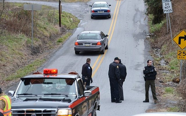 Local law enforcement block off a road near Canoe Creek State Park, Pa. while investigating a shooting on Friday. The suspect fired at troopers responding to other shootings Friday morning. The fleeing gunman then crashed head-on into a trooper's car and got out of his truck and shot again at police, who returned fire and killed him. (photo credit: AP Photo/Altoona Mirror, J.D. Cavrich)