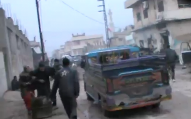 Rebel fighters rush to the scene of a Syrian airstrike on a bakery (at right) in Halfaya, where more than 60 people were reported killed on Sunday. (photo credit: image capture from YouTube video)