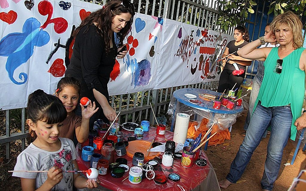 Children in Ramat Hasharon paint with volunteers from Takdim, an Israeli charity modeled on the Jewish federation system in the US. (Courtesy of Takdim via jTA)