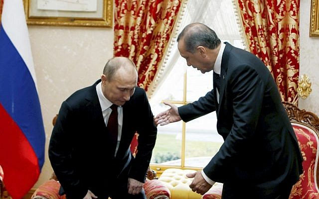 Russian President Vladimir Putin sits down as Turkey's then-prime minister Recep Tayyip Erdogan looks on before a meeting in Istanbul, Turkey, December 3, 2012. (AP/Tolga Bozoglu, Pool)