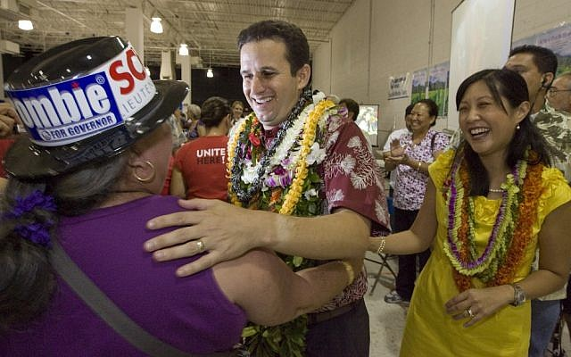 A supporter congratulates then-Lt. governor-elect Brian Schatz, center, as his wife Linda looks on in 2012 (photo credit: Eugene Tanner/AP, File)
