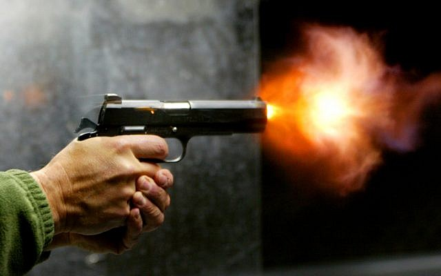 A man fires his handgun (photo credit: Olivier Fitoussi/Flash90)
