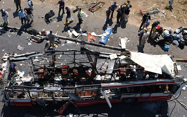 Police and paramedics inspect the scene after a suicide bomber blew himself up on a rush-hour bus near the Jerusalem neighborhood of Gilo during the Second Intifada, on June 18, 2002 (Flash90/File)