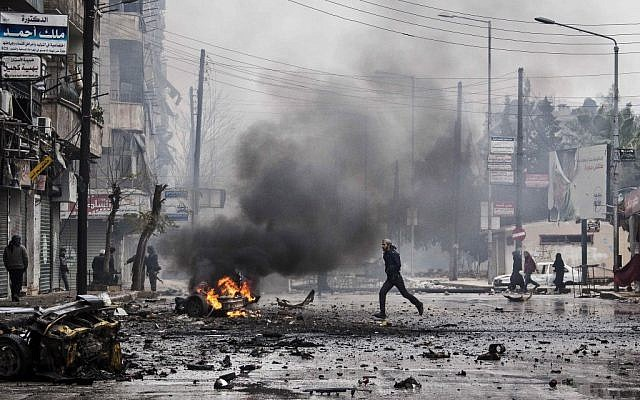 A man runs through the debris after a mortar shell hit a street, killing several people, in the Bustan Al-Qasr district of Aleppo, Syria, December 2012 (photo credit: AP/Narciso Contreras)