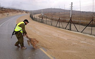 Illustrative: A tracker helping to mop up tracks along the West Bank security fence. (Mitch Ginsburg/The Times of Israel)