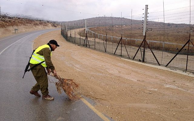 A tracker helping to mop up the tracks along the West Bank security fence (Photo credit: Mitch Ginsburg/ Times of Israel)