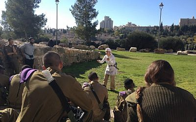 An actor with the Western Wall Heritage Foundation speaking to the soldiers on their way to the Western Wall (photo credit: Mitch Ginsburg/Times of Israel)