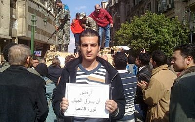 """Maikel Nabil in Cairo's Tahrir Square holding a sign saying """"Refusing to let the army steal the people's revolution"""" (photo credit: courtesy)"""
